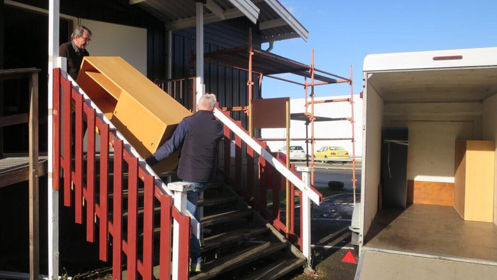 Två män bär en möbel nerför en trappa utomhus.